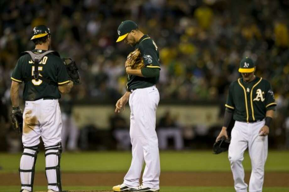Jim Johnson of the Oakland Athletics stands on the pitchers mound next to John Jaso (5) and Josh Donaldson (20) after giving up a run against the Houston Astros during the eighth inning at O.co Coliseum on July 23, 2014 in Oakland, California. Photo: Jason O. Watson, Getty Images