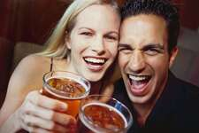 close-up of a young couple laughing with glasses of beer in their hands cocktail bar man woman alcohol 