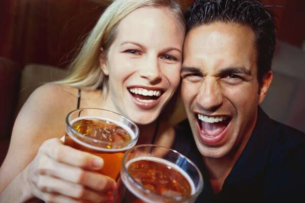 close-up of a young couple laughing with glasses of beer in their hands cocktail bar man woman alcohol By: Stockbyte Collection: Stockbyte