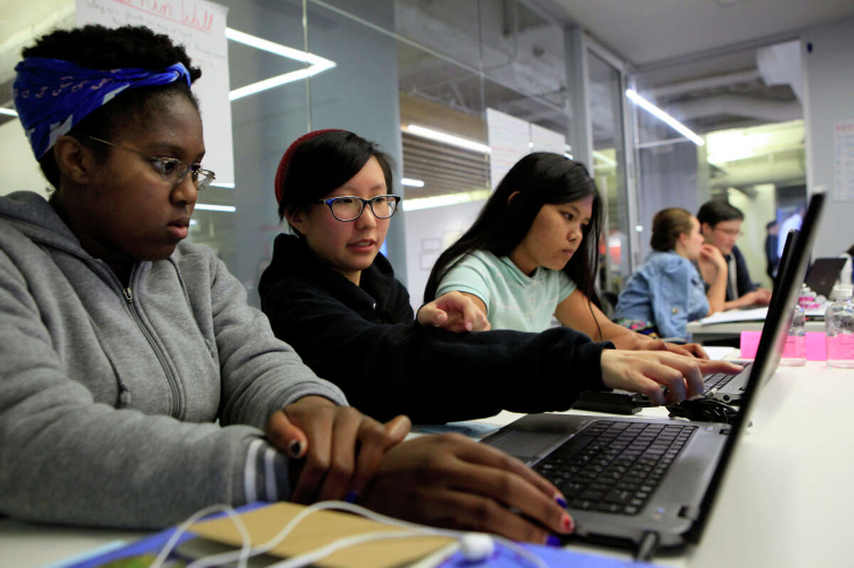Teaching assistant Angela Xu, center, works with Mesoma Esonwune, left, and Deanne Estigoy during a Girls Who Code class for young women at Square headquarters in San Francisco, CA, Friday, July 18, 2014.