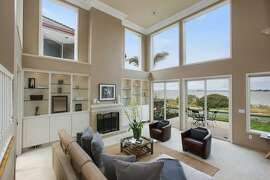 The two-story living room features massive picture windows and sliding doors opening to a backyard with bay views.