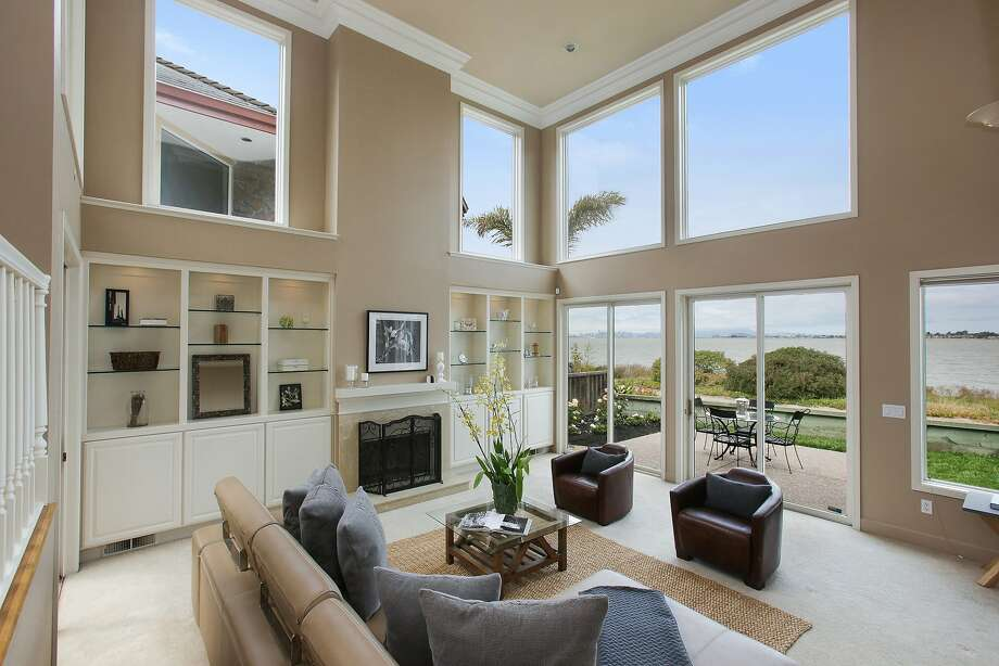 The two-story living room features massive picture windows and sliding doors opening to a backyard with bay views. Photo: OpenHomesPhotography.com