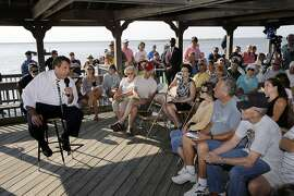 "New Jersey Gov. Chris Christie, seated left, answers a question about pensions from retired Stafford Township, N.J., Police Chief Larry Parker, right front, as Christie addressed a gathering Tuesday, July 22, 2014, in Long Beach Township, N.J. The possible 2016 Republican presidential contender is calling his talks ""No Pain, No Gain,"" and he's sounding alarms — as he has for much of the year — that the state's promised pension and health benefits for public sector workers are becoming unaffordable. He offers the bankruptcy of Detroit as a warning sign for his state. (AP Photo/Mel Evans)"