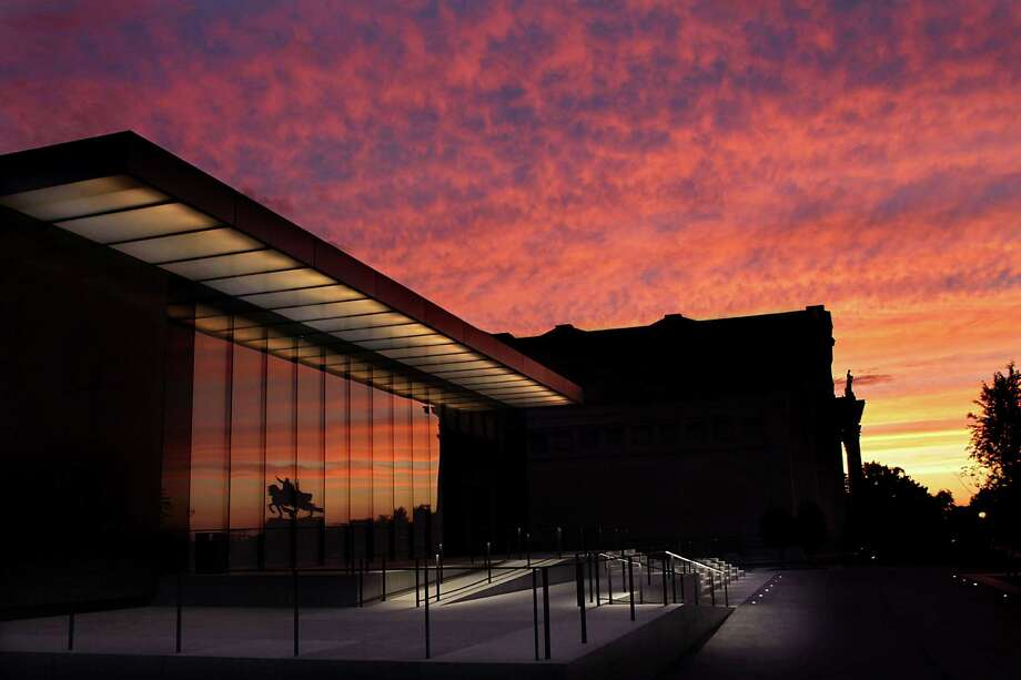 The sun sets over Forest Park and the new St. Louis Art Museum East Building on Thursday, June 6, 2013.  Reflected in the front windows is the statue of King Louis IX of France, which stands over Art Hill. (Robert Cohen) Photo: Robert Cohen / St. Louis Post-Dispatch
