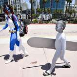 Dina Mills, left, and her son walk outside of the convention center on day 1 of the 2014 Comic-Con International Convention held Thursday, July 24, 2014 in San Diego.