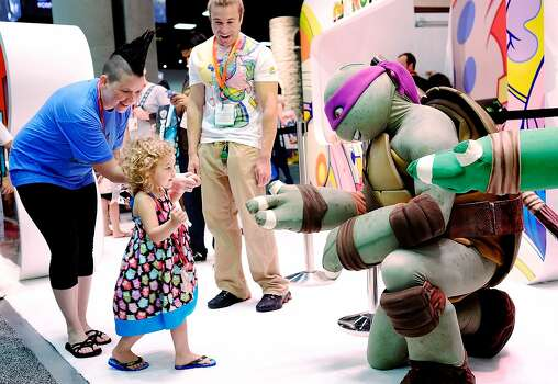 Two year old Ellie Campbell, along with her aunt Jen Pike of Austin, Texas, gets a high-five from the Teenage Mutant Ninja Turtle character Donatello during the 45th annual San Diego Comic-Con on July 24, 2014 in San Diego, California. An estimated 130,000 attendees are expected at this year's convention, which will celebrate the 75th anniversary of both Marvel Comics and the first Batman comic book. Photo: T.J. Kirkpatrick, Getty Images