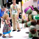 Two year old Ellie Campbell, along with her aunt Jen Pike of Austin, Texas, gets a high-five from the Teenage Mutant Ninja Turtle character Donatello during the 45th annual San Diego Comic-Con on July 24, 2014 in San Diego, California. An estimated 130,000 attendees are expected at this year's convention, which will celebrate the 75th anniversary of both Marvel Comics and the first Batman comic book.