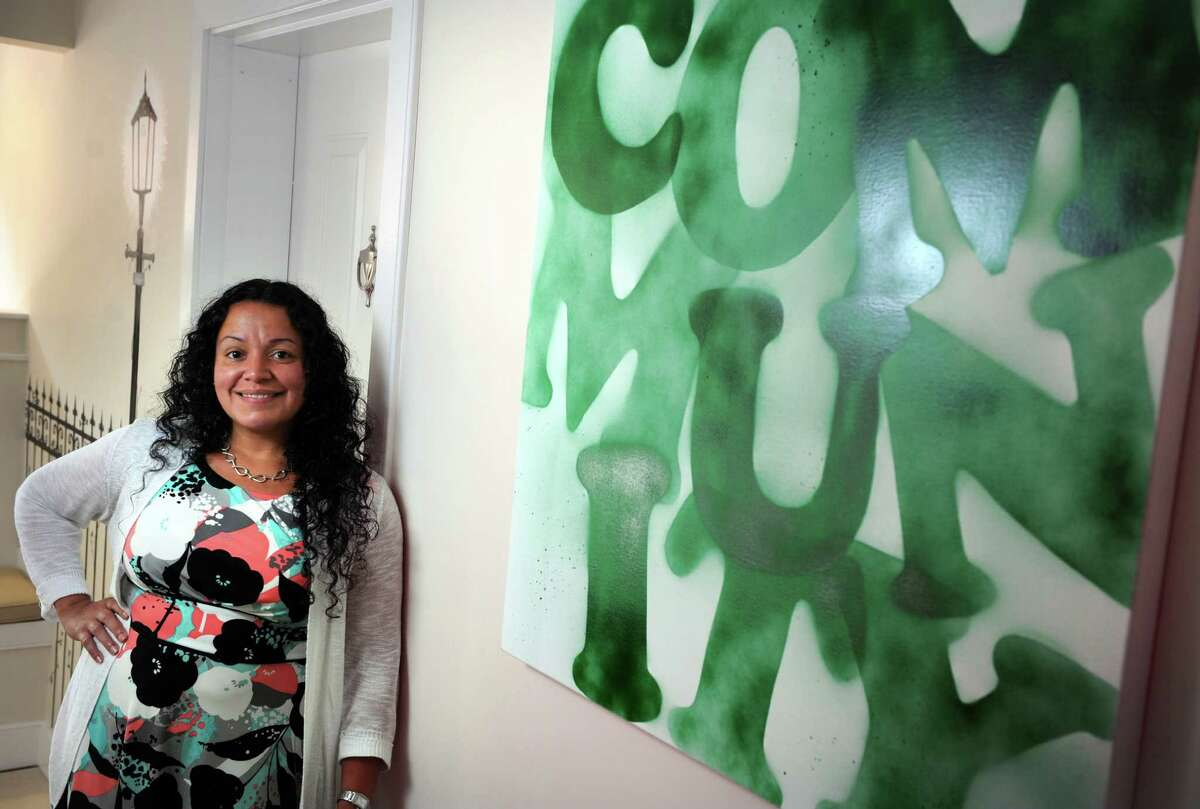 Liz Torres, executive director of Bridgeport Neighborhood Trust, a nonprofit that develops properties and offers homeownership counseling, stands in the group's new office on State Street in Bridgeport, Conn.