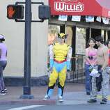 A fan dressed as Wolverine from the X-Men waits at a crosswalk on day 1 of the 2014 Comic-Con International Convention held Thursday, July 24, 2014 in San Diego.