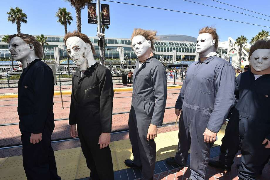"""People dressed as serial killers from movie """"Halloween"""" wait at the trolley stop outside of the convention center on day 1 of the 2014 Comic-Con International Convention on Thursday, July 24, 2014 in San Diego. Photo: Denis Poroy, Associated Press"""