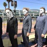 """People dressed as serial killers from movie """"Halloween"""" wait at the trolley stop outside of the convention center on day 1 of the 2014 Comic-Con International Convention on Thursday, July 24, 2014 in San Diego."""