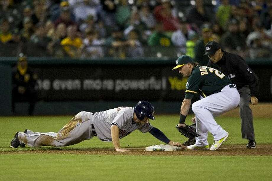 Robbie Grossman slides into third base ahead of a tag from Josh Donaldson in front of umpire Adam Hamari during the eighth inning. Photo: Jason O. Watson, Getty Images