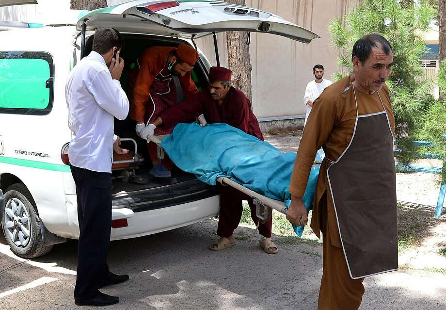 Afghan medical workers carry one of the bodies of two foreign women who were gunned down by men on a motorcycle, at the morgue of Herat hospital on July 24, 2014.  Two foreign female aid workers were shot dead by unknown gunmen while travelling in a taxi in the western Afghan city of Herat, officials said.   AFP PHOTO/Aref KarimiAref Karimi/AFP/Getty Images Photo: Aref Karimi, AFP/Getty Images