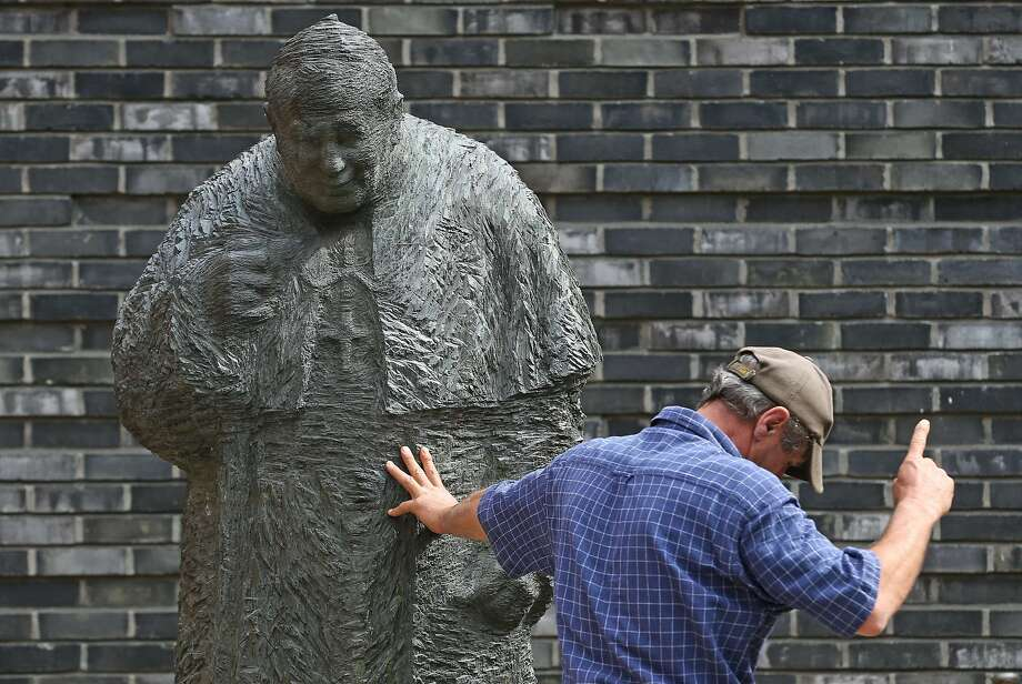 About this doctrine of infallibility ...A worker in Hamburg, Germany, is either installing the  bronze   statue of Pope John Paul II at St. Mary's Cathedral or debating it. Photo: Axel Heimken, AFP/Getty Images