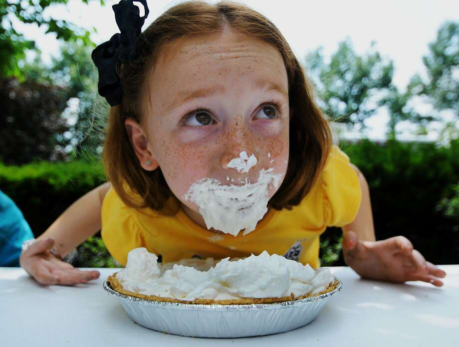 Too much on her plate: Seven-year-old Isabella Fasula comes up for air during the pie-eating contest at the Holy Family 