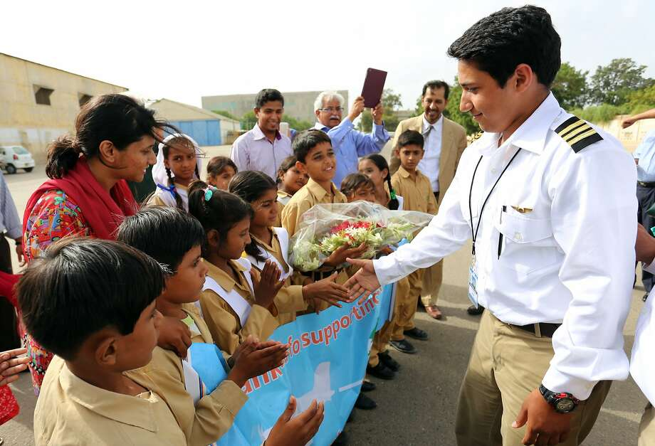 Haris Suleman is greeted by students from the Citizens Foundation school in Lahore, Pakistan, earlier in July at a stop in his father's homeland during his around-the-world flight. Photo: Associated Press