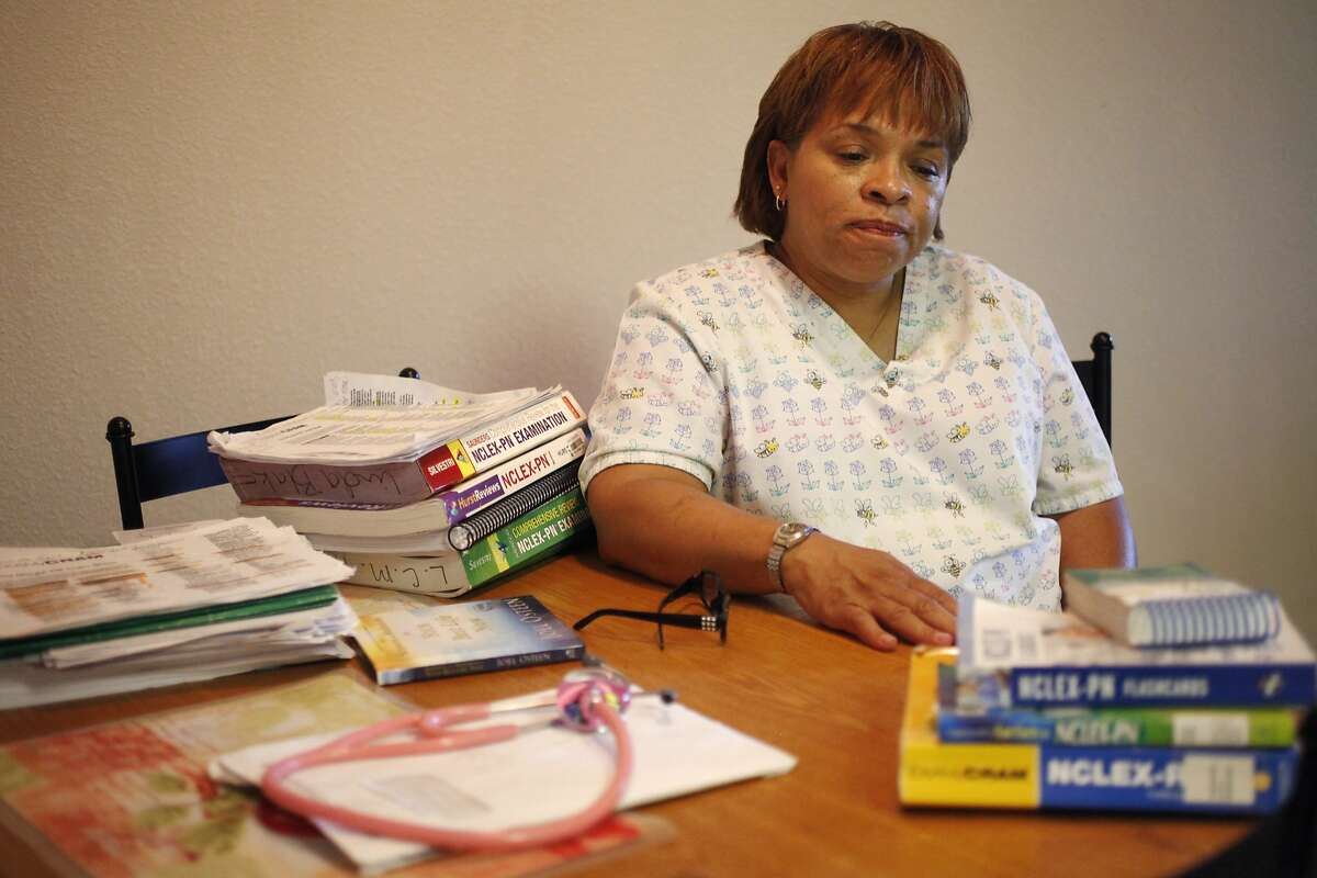 """Linda Blake, 54, a Certified Nursing Assistant and a Home Health Aid, pictured with her study materials June 5, 2014 at her home in Fairfield, Calif. Blake graduated from a Licensed Vocational Nursing program at Intercoast in September 2013. She doesn't feel like the school adequately equipped her for the exam. Since then, she has spent $300 on a Hurst review course and has failed the test once, which costs $350 and can be taken up to eight times. """"I don't want this to happen to anyone else,"""" she said of the experience."""
