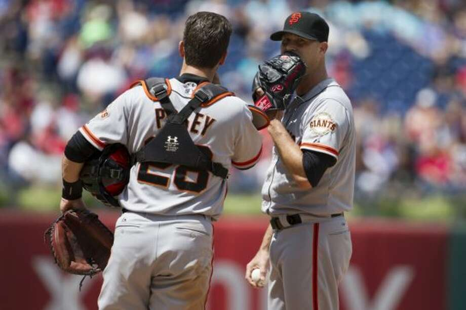 San Francisco Giants starting pitcher Tim Hudson, right, talks things over with catcher Buster Posey, left, during the fourth inning of a baseball game against the Philadelphia Phillies, Thursday, July 24, 2014, in Philadelphia. The Phillies won 2-1. Photo: Chris Szagola, Associated Press