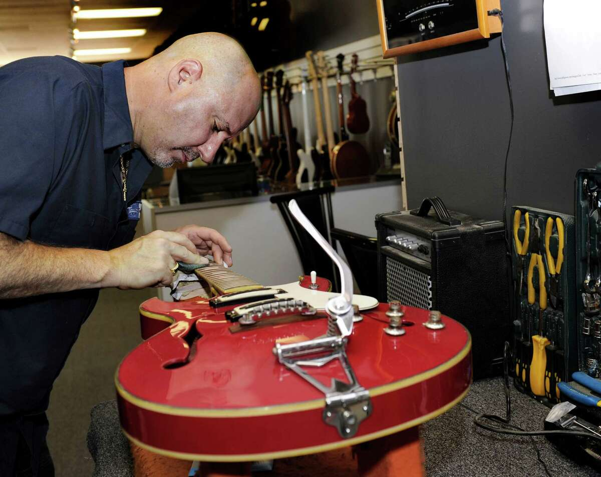 Rick Tedesco, owner of Guitar Hangar, polishes the frets on a guitar at his Brookfield, Conn. store, photographed in his store, Wednesday, July 23, 2014.