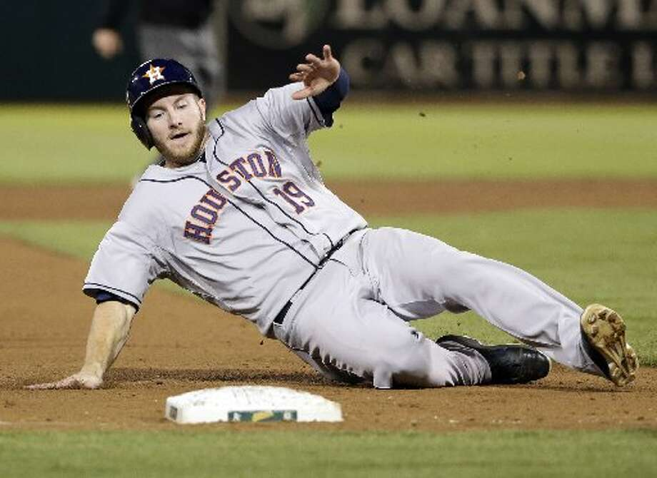 Robbie Grossman slides safely into third base after a single by Jon Singleton during the eighth inning. Photo: Associated Press