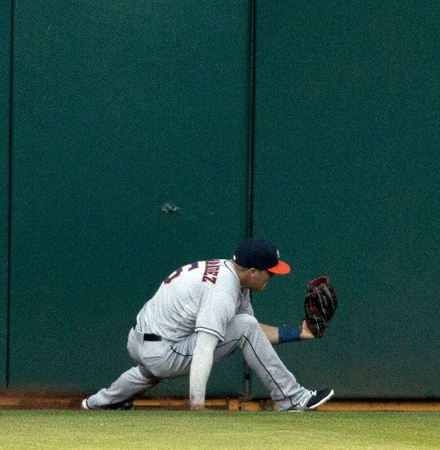 Astros center fielder Enrique Hernandez falls to his knees after making a basket catch of the Oakland Athletics' John Jaso's sacrifice fly during the second inning. Photo: D. Ross Cameron, MCT