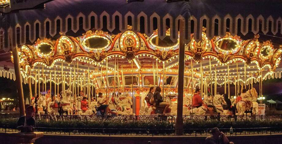 Fantasyland's merry-go-round, known as the King Arthur Carrousel, attracts visitors day and night. It looks even more spectacular after sunset. Photo: Dino Chiecchi / San Antonio Express-News / San Antonio Express-News