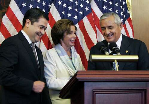 House Democratic Leader Nancy Pelosi, D-Calif., center, is seen with Guatemalan President Otto Molina, right, and Honduran President Juan Hernández on Thursday, July 24, 2014 on Capitol Hill in Washington. (AP Photo/Lauren Victoria Burke) Photo: Lauren Victoria Burke, Associated Press / FR132934 AP