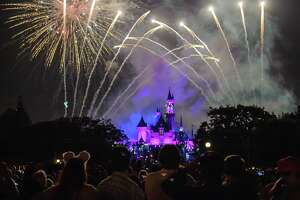 Thousands of park visitors gather on Main Street, U.S.A., for the best view of the nightly fireworks display at Disneyland. The castle lights up, changes colors and Tinker Bell (in the middle left of the photo) greets patrons as the show begins.