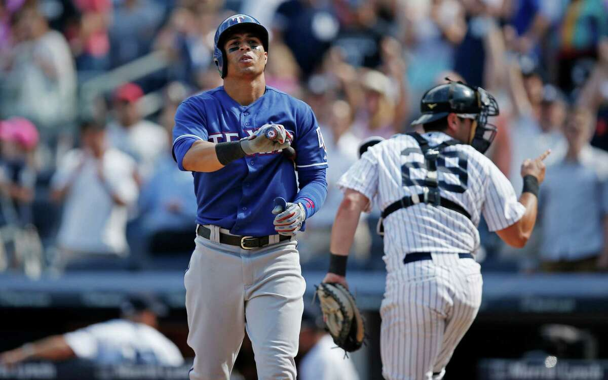 Texas Rangers Leonys Martin reacts after striking out to end the Texas Rangers 4-2 loss to the New York Yankees in a baseball game at Yankee Stadium in New York, Thursday, July 24, 2014. New York Yankees catcher Francisco Cervelli (29) turns to the umpire to confirm the strikeout. (AP Photo)