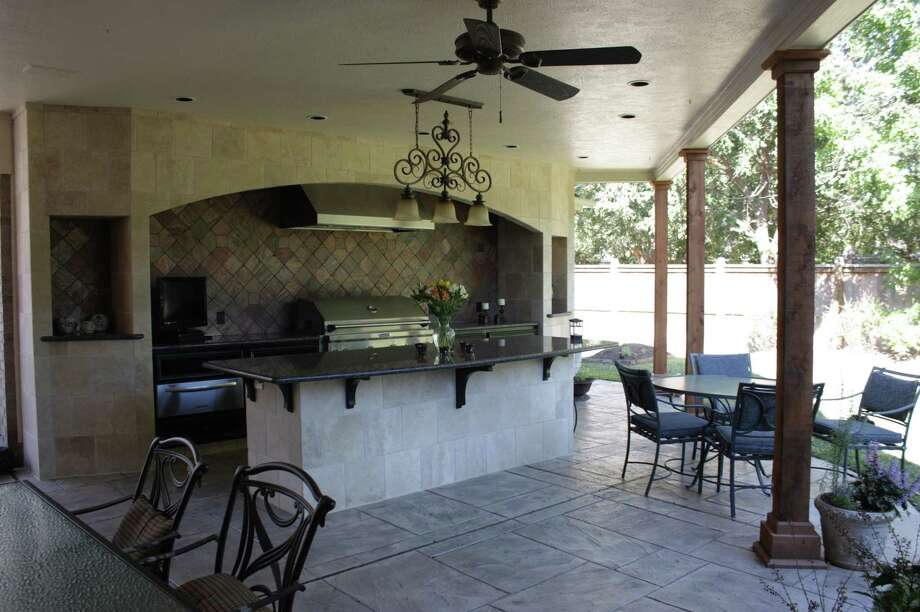 The ceiling fan accents the decor of this outdoor living space created by Charanza Contracting.