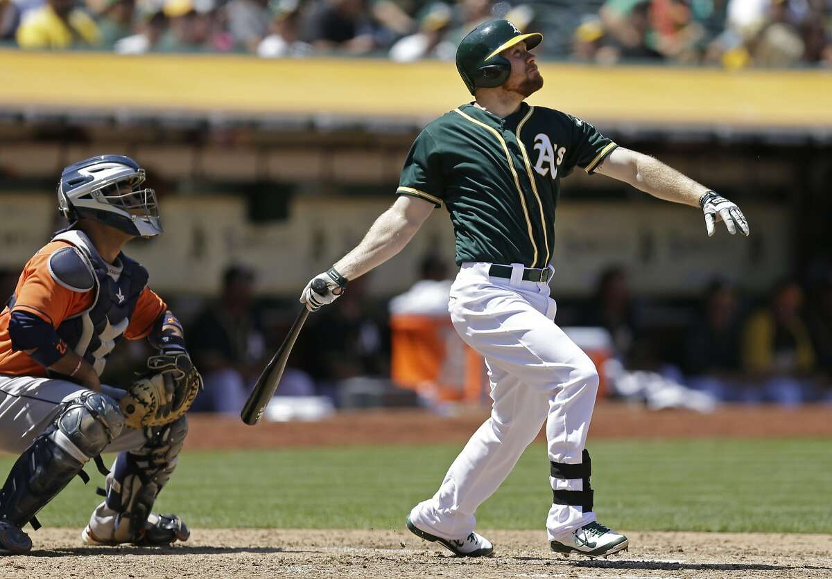 Oakland Athletics' Brandon Moss, right, swings for a grand slam off Houston Astros' Anthony Bass in the sixth inning of a baseball game on Thursday, July 24, 2014, in Oakland, Calif. (AP Photo)