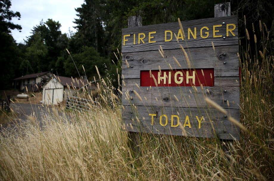 FILE PHOTO: Dry grasses partially cover a fire danger sign that is posted in Samuel P. Taylor state park on July 15, 2014 in Lagunitas, California. Photo: Justin Sullivan, Getty Images / 2014 Getty Images
