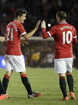 Manchester United's Ander Herrera, left, and Wayne Rooney celebrate a goal by Danny Welbeck during the first half of a friendly soccer match against the Los Angeles Galaxy at the Rose Bowl on Wednesday, July 23, 2014, in Pasadena, Calif. (AP Photo)