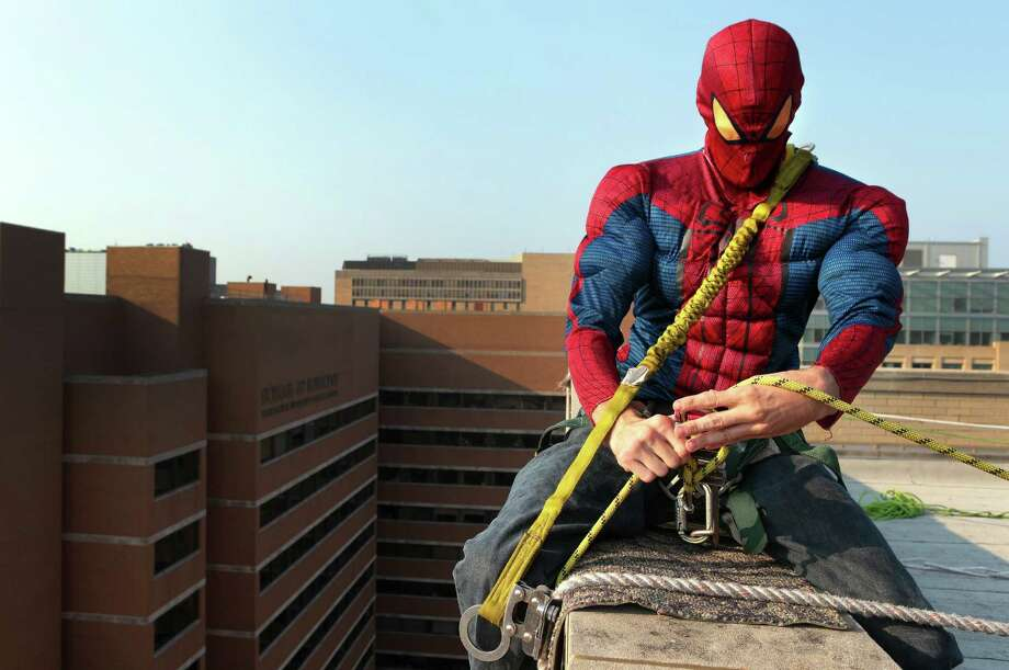 "In this photo taken on Tuesday, July 22, 2014, Andy Weeks, wearing a Spider-Man costume, readies his ropes as he climbs over the roof of St. Louis Children's Hospital to wash patient windows in St. Louis. ""You go over the wall and everyone screams your name,"" said Weeks.  ""Then you come back and it's back to being you.""  Photo: Robert Cohen, Associated Press / St. Louis Post-Dispatch"