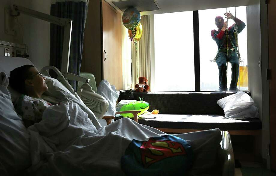 In this photo taken on Tuesday, July 22, 2014, Andy Weeks, wearing a Spider-Man costume, peers into the room of patient Jacob Rodriguez, 10, of Glendale, as Weeks washes windows at St. Louis Children's Hospital in St. Louis. Photo: Robert Cohen, Associated Press / St. Louis Post-Dispatch