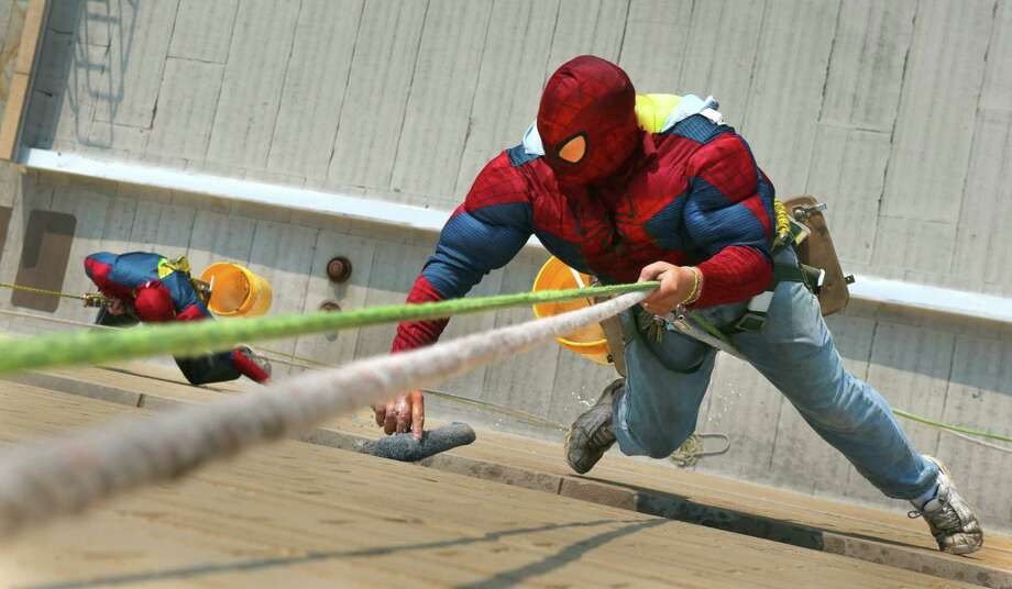 Matt McGehee, right, and Andy Weeks, of Allglass,  don Spider-Man costumes as they surprised patients while washing the windows at St. Louis Children's Hospital in St. Louis. Photo: Robert Cohen, Associated Press / St. Louis Post-Dispatch