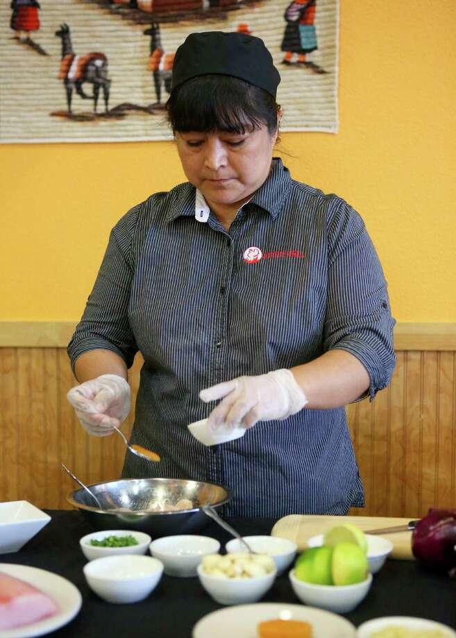 Head chef Damaris Trinidad adds puréed rocoto pepper to the ceviche mixture. Photo: Photos By Timothy Tai / San Antonio Express-News / © 2014 San Antonio Express-News