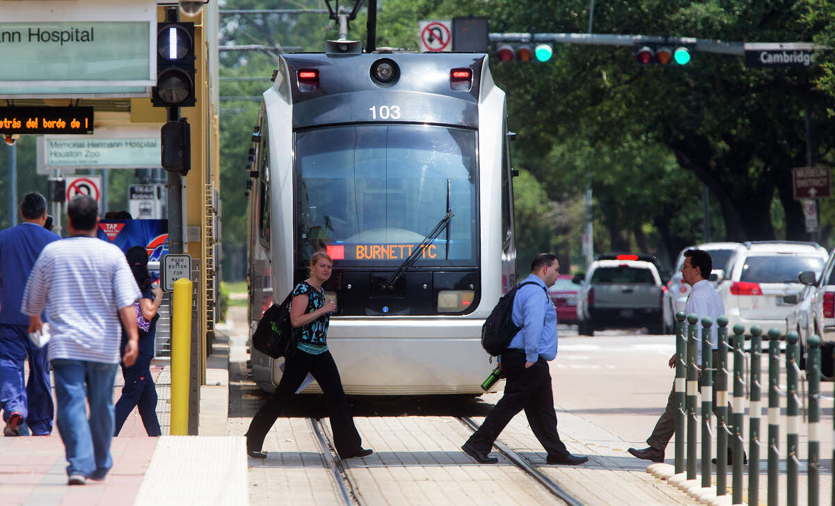 A METRO rail makes its way along the track as a group of pedestrians cross Fannin Street in the Texas Medical Center on July 24.
