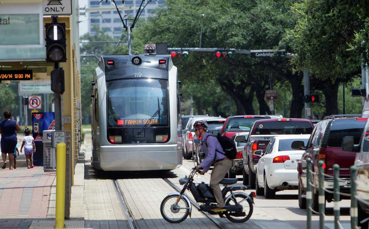 A METRO rail makes its way along the track as a pedestrian crosses Fannin Street in the Medical Center, Thursday, July 24, 2014, in Houston.