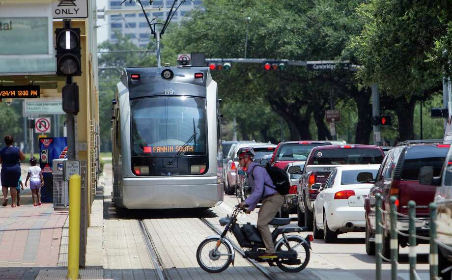 A METRO rail makes its way along the track as a pedestrian crosses Fannin Street in the Medical Center, Thursday, July 24, 2014, in Houston. Photo: Cody Duty, Houston Chronicle / © 2014 Houston Chronicle