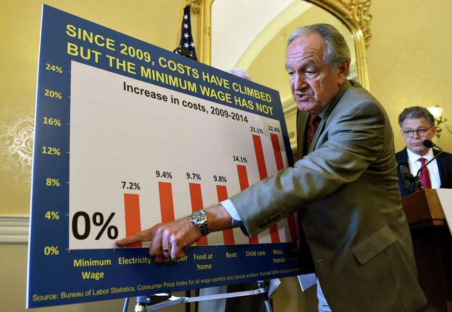 Sen. Tom Harkin, D-Iowa, joined by Sen. Al Franken, D-Minn.,    points out the zero percent increase in the minimum wage. If Congress and the Texas Legislature don't raise it, cities across the state should. Photo: Associated Press / AP