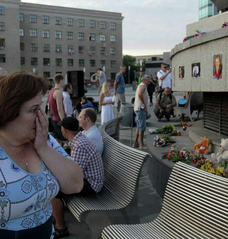 People look at pictures of the victims of the Malaysian Airlines crash at a memorial built in a central square in Kharkiv, Ukraine. Photo: Sergei Chuzavkov / Associated Press / AP