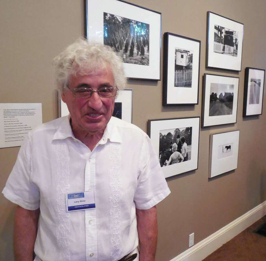 "Well-known photographer and long-time resident, Larry Silver, stands besides some of the dozens of his images of Westport now on exhibit at the Westport Historical Society. Thursday was the opening night of the exhibit, ""Larry Silver/Westport Visons,"" which runs through Oct. 18. Photo: Anne M. Amato / westport news"