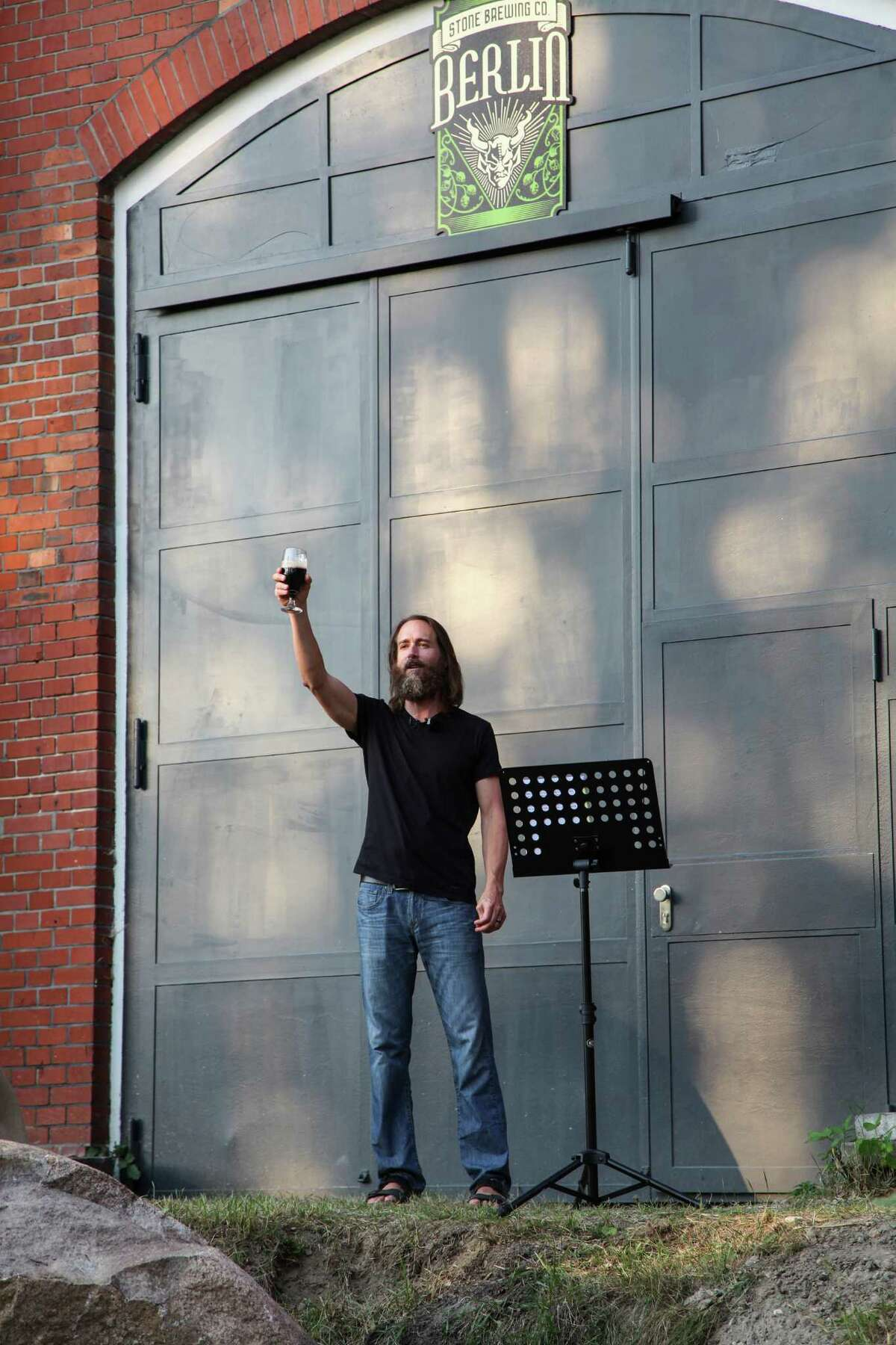 Stone Brewing Co. CEO and co-founder Greg Koch addresses crowd outside what will be the main hall of Stone Brewing Co.'s first European brewery. Shown here on July 19, 2014, when the project was formally announced.
