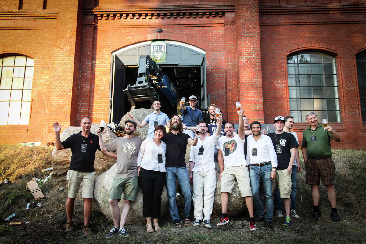 Stone Brewing Co. CEO and co-founder Greg Koch, center in dark shirt, raises a toast this month with a crowd in Berlin outside what will be the main hall of Stone's first European brewery.