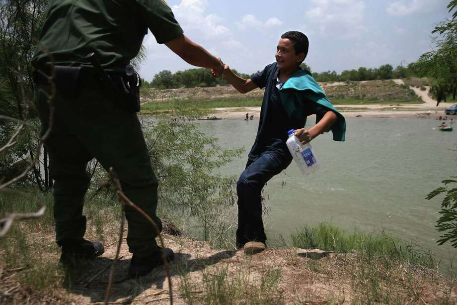 A U.S. Border Patrol agent assists an unaccompanied 13-year-old from El Salvador after he crossed the Rio Grande into the United States on Thursday near Mission, Texas. Photo: John Moore, Staff / 2014 Getty Images