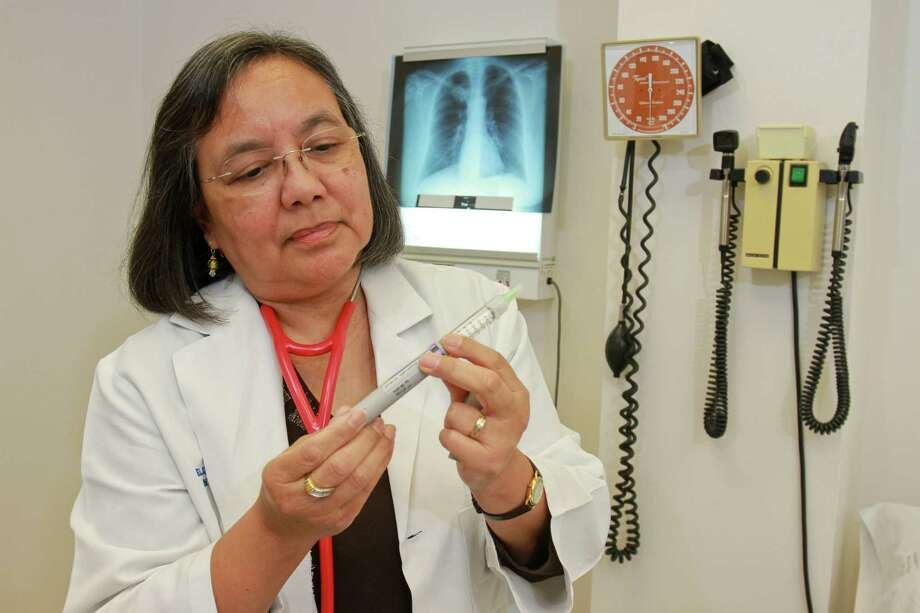 Dr. Elizabeth Torres, president of the Harris County Medical Society, with a Lantus SoloStar Insulin Pen. She said that she learned about the device, which helps people better inject their insulin, because a drug rep showed it to her in her office and left free samples for Torres' patients. Photo: Gary Fountain, Freelance / Copyright 2014 by Gary Fountain