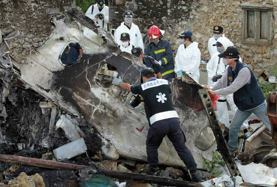 A forensic team recovers human remains among the wreckage of crashed TransAsia Airways flight GE222 on the outlying island of Penghu, Taiwan, Thursday, July 24, 2014. Stormy weather on the trailing edge of Typhoon Matmo was the likely cause of the plane crash that killed more than 40 people, the airline said. Aviation has suffered one of its worst weeks in memory, a cluster of disasters spanning three continents. (AP Photo/Wally Santana) Photo: Wally Santana, STF / AP