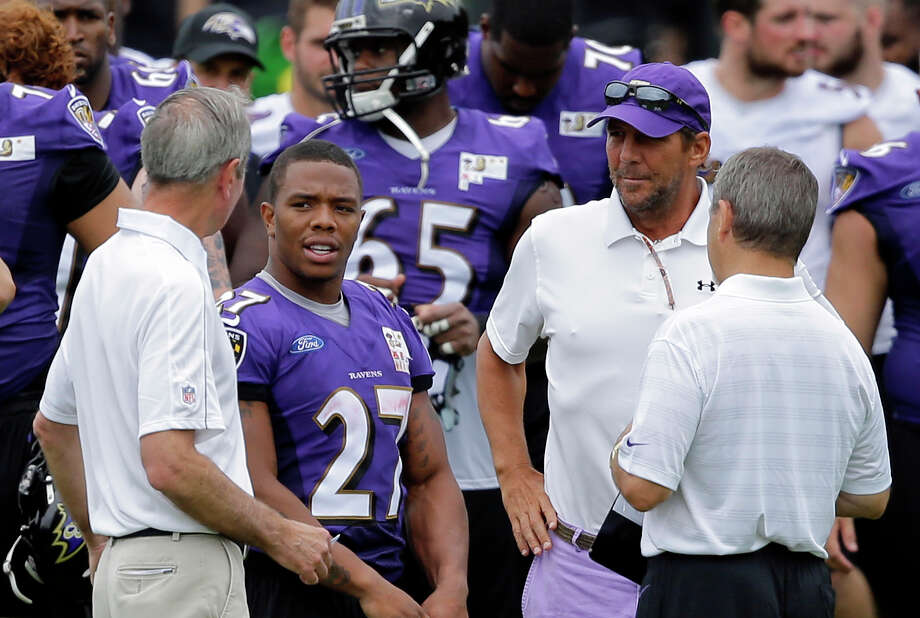 Baltimore Ravens running back Ray Rice, second from left, speaks with team president Dick Cass, left, owner Steve Bisciotti, second from right, and Kevin Byrne, senior vice president for public and community relations, after a training camp practice, Thursday, July 24, 2014, at the team's practice facility in Owings Mills, Md. (AP Photo) ORG XMIT: MDPS117 / AP