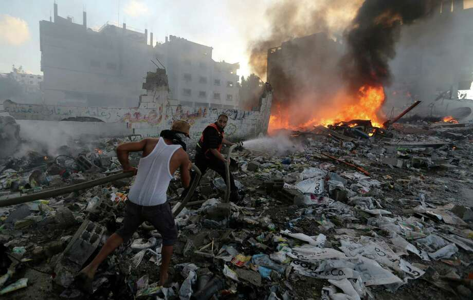 Palestinian men try to extinguish flames in an area damaged in an Israeli airstrike in Gaza. Israeli tanks and warplanes bombarded the Gaza Strip on Thursday, the bloodiest day of the 17-day war. Photo: Hatem Moussa / Associated Press / AP